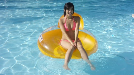 Thumbnail for Lovely Young Woman Floating In a Swimming Pool