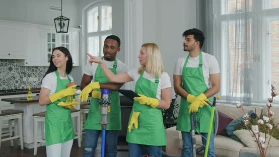 Woman Giving Commands to Cleaning Staff while they Together Visiting Customer House
