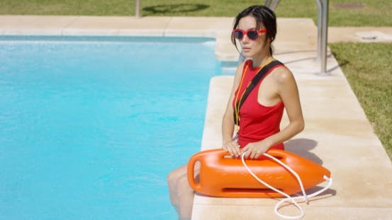 Serious Lifeguard Sitting At Side Of Pool