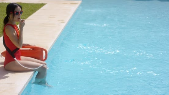 Thumbnail for Lifeguard Using Whistle While Sitting In Pool
