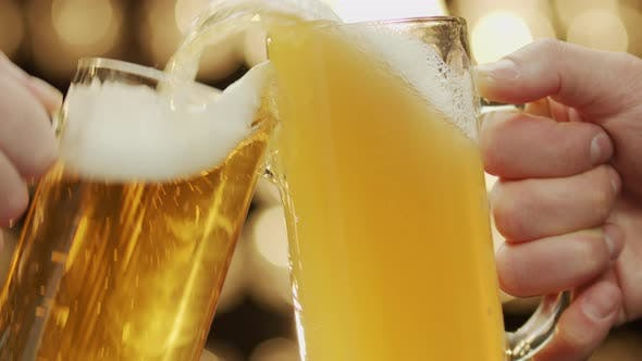 Two friends toast beer mugs spilling beer close-up bokeh background