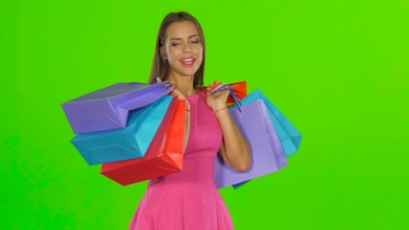 Thumbnail for Woman Smiling While Holding Shopping Bags