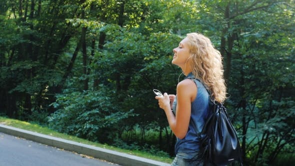 Thumbnail for Attractive Woman Walking In The Park, Listening To Music. Back View