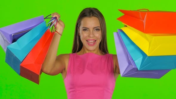 Thumbnail for Woman Joyfully Looks Out From Behind Shopping Bags. Green Screen.