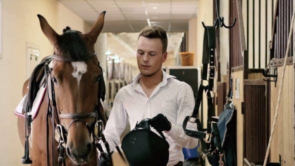 Thumbnail for Junge Mann setzen auf den Helm in der Nähe des Pferdes