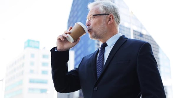 Thumbnail for Senior Businessman Drinking Coffee On City Street