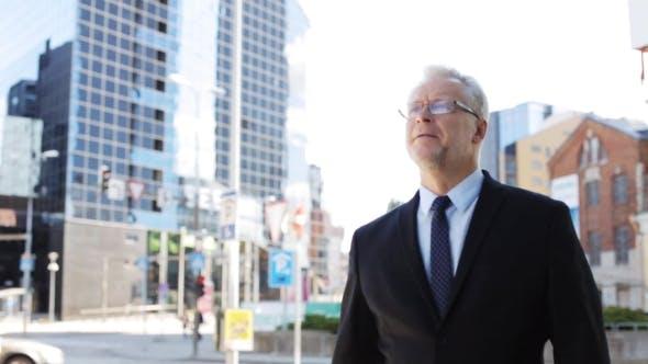 Thumbnail for Senior Businessman Walking Along City Street