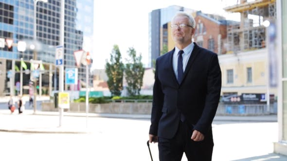 Thumbnail for Senior Businessman Walking With Travel Bag In City