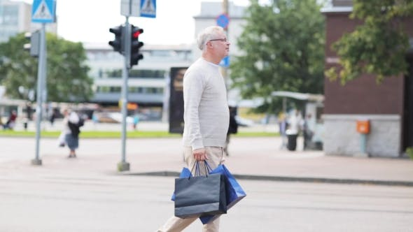 Thumbnail for Senior Man With Shopping Bags Walking In City