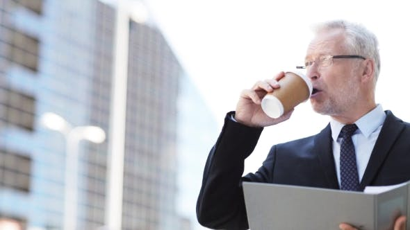 Thumbnail for Senior Businessman With Coffee And Folder In City