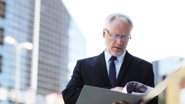 Thumbnail for Senior Businessman With Ring Binder Folder In City