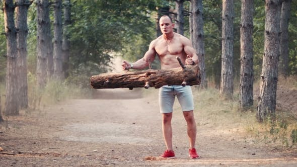 Thumbnail for Shirtless Bodybuilder Doing Curlings With Log on Forest Road