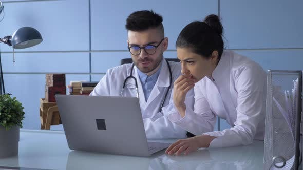 Close Up A Portrait Of Man And Woman Doctor With Laptop Sitting In Hospital Office.