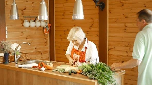 Cover Image for Eine alte Frau in der Küche schneiden Karotten.