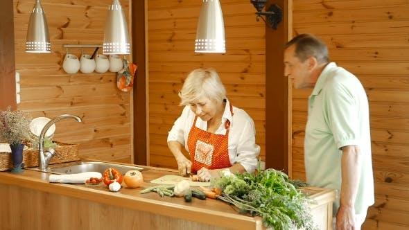 Thumbnail for Älterer Mann nimmt geschnittene Karotten aus dem Tisch.