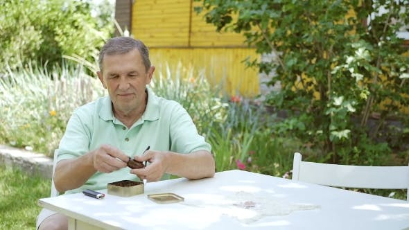 Thumbnail for Der Mann steckt Tabak in seine Pfeife.