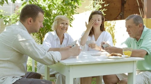 Family Playing Cards In The Garden.