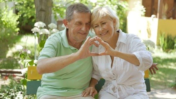 Thumbnail for Elderly Couple Hands Show Heart.