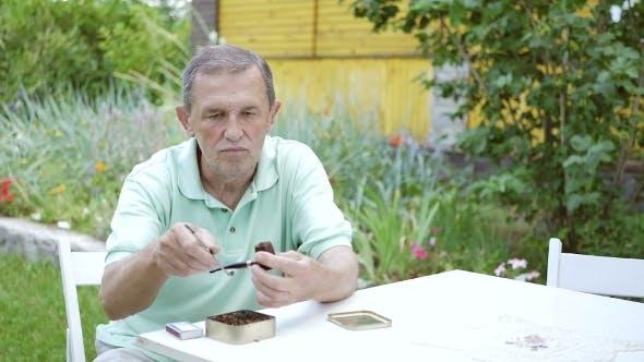 Thumbnail for Ein Mann zündet eine Pfeife mit Tabak.