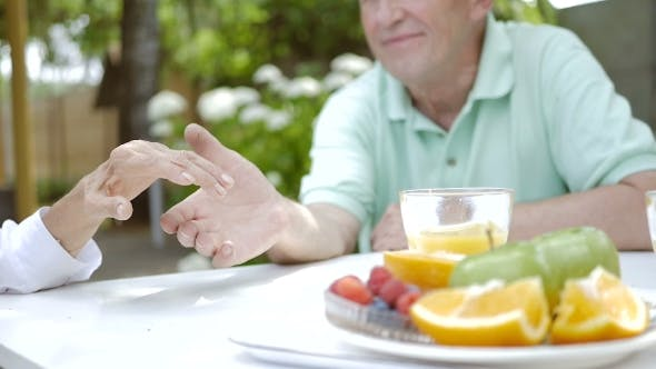 Thumbnail for Elderly Couple Holding Hands In a Garden.