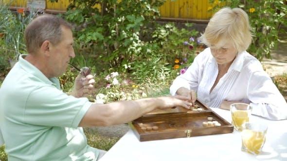 Elderly Couple Playing Backgammon In The Garden.