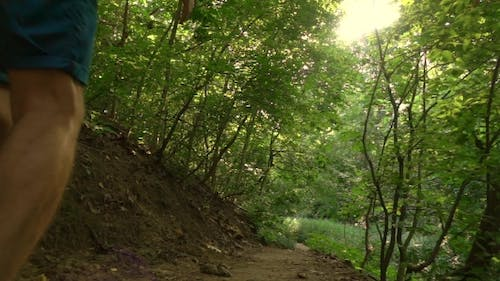 Man Running Uphill In The Woods
