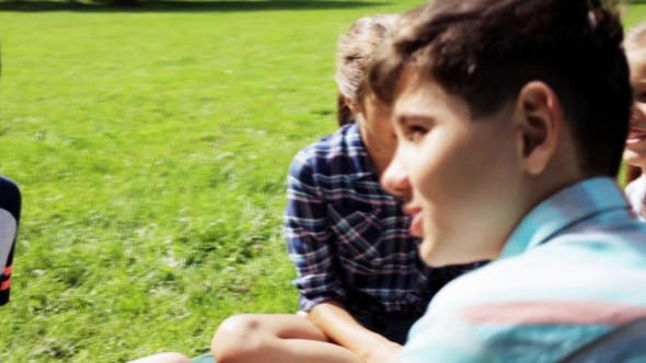 Thumbnail for Group Of Happy Kids Sitting On Grass And Talking 17