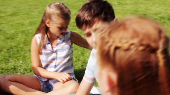 Thumbnail for Group Of Happy Kids Sitting On Grass And Talking 19