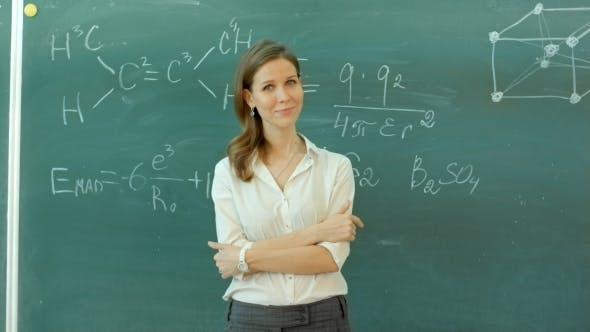 Thumbnail for Young Happy Female Teacher With Arms Crossed Standing Against Green Board