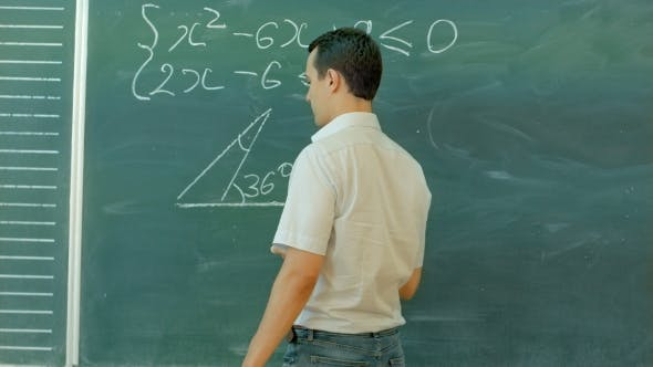 Thumbnail for Young Male Teacher Or Student Holding Chalk Writing On Chalkboard In Classroom