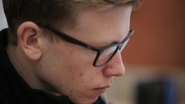 Thumbnail for Young Man In Black-rimmed Glasses With a Serious Face Pimples, And Reflection Of Laptop Screen, .