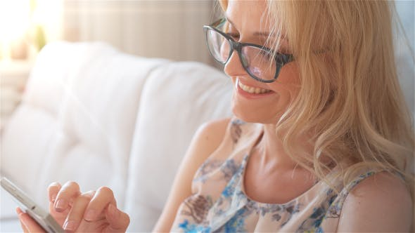 Thumbnail for Happy Smiling Girl Using SmartPhone Sitting on Sofa at Home 3