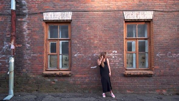 Thumbnail for Schöne Frau posiert bei der alten Backstein Haus