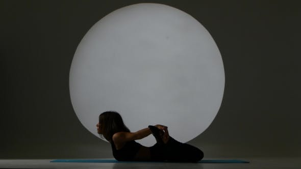 Thumbnail for Girl In Pose On The Stomach Does Stretch. Back Light. Silhouette