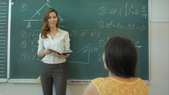 Thumbnail for Teacher Teaching Mathematics On Chalkboard In Classroom