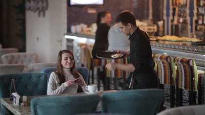 A Young Woman Brings Order In a Restaurant.