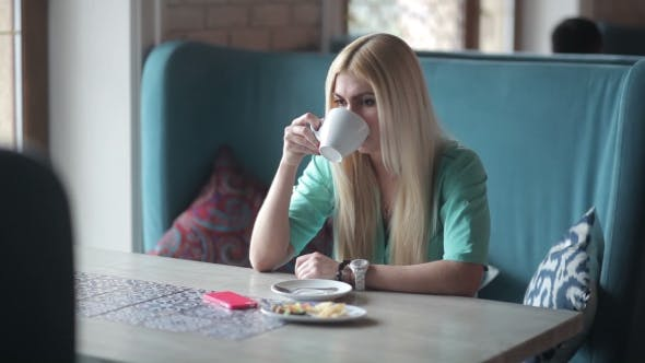Cover Image for Blonde Drinking Coffee And Looking At Her Watch.