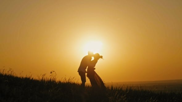 Thumbnail for Romantic Silhouette Of Man On High Hill - At Sunset - Kissing And Dancing