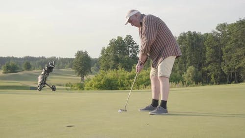 Cute Old Man Playing Golf Alone on the Golf Field. Senior Man Hit the Ball Using Golf Club. The Guy