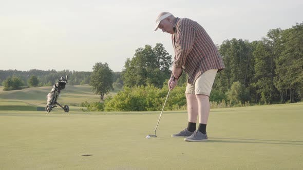Thumbnail for Cute Old Man Playing Golf Alone on the Golf Field. Senior Man Hit the Ball Using Golf Club. The Guy