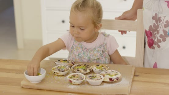 Thumbnail for On Girl Sprinkling Toppings On Muffins