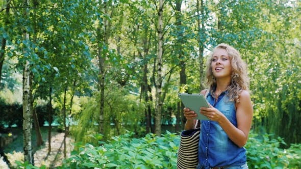 Thumbnail for Attractive Woman Walking With a Tablet in the Park, Looking at the Map
