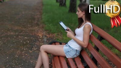 Woman Reading Ebook on a Park Bench