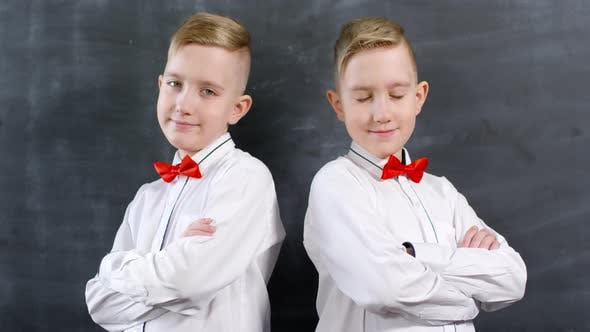 Thumbnail for Dressed-Up Caucasian Twins Posing against Chalkboard