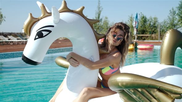 Thumbnail for Beautiful Girl In Swimsuit Lies On Air Mattress In Outdoor Pool Near Palm 20s