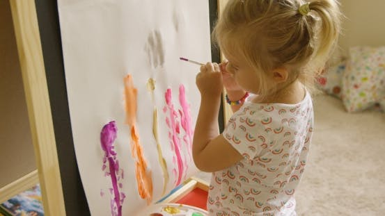 Thumbnail for Little Girl Standing Painting At An Easel