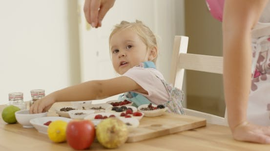 Thumbnail for Child Watching Woman Sprinkle Candy On Muffins