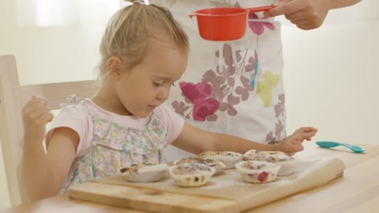 Cover Image for Child Interested In Sugar Falling On Baked Muffins