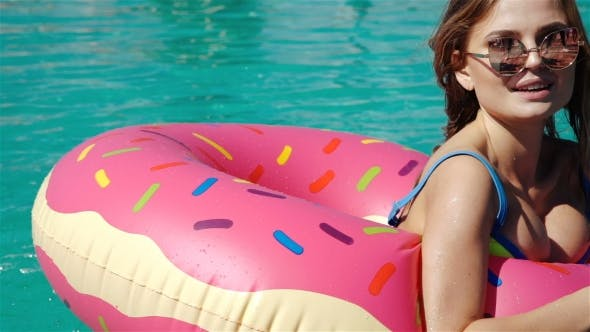 Thumbnail for Gorgeous Young Woman With Sunglasses In Black Bikini Lying In Inflatable Pink Donut Float In Pool