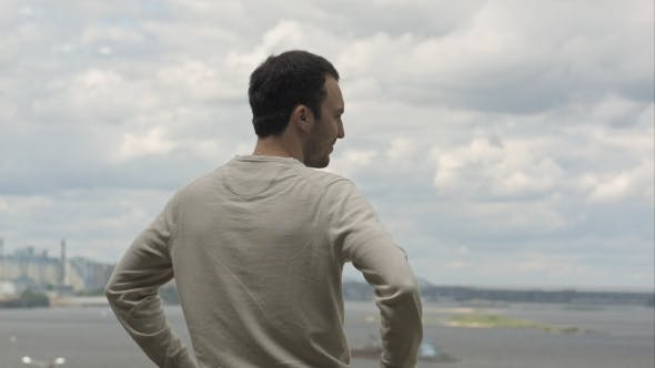 Thumbnail for Young Man Is Looking Into The Distance To The River On a Cloudy Day.